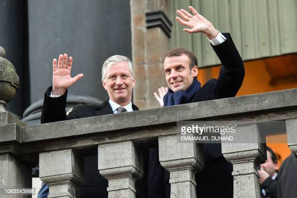 King Philippe of Belgium and French President Emmanuel Macron wave to the crowd from the balcony at the city hall in Ghent, on November 19 during a...