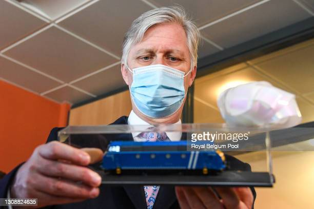 King Philippe of Belgium looks at a miniature toy train during his visit to the train-station Ottignies on March 24, 2021 in Ottignies-Louvain-la...