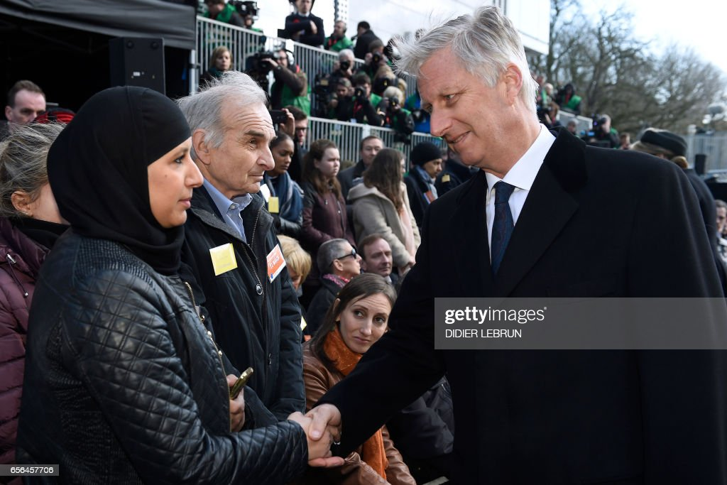 King Philippe of Belgium (R) meets people during the inauguration of a steel memorial by Belgian sculptor Jean-Henri Compere at the heart of the European Union institutions based in Brussels as the country marks the first anniversary of the twin Brussels attacks by Islamic extremists on March 22, 2017. A year on from the attacks led by an Islamic State cell that was also responsible for the November 2015 Paris attacks, Belgium remains on high alert with troops patrolling the streets and warnings of fresh risks. / AFP PHOTO / POOL / Didier Lebrun / Belgium OUT
