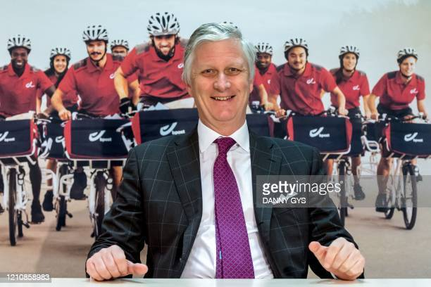 King Philippe of Belgium poses as he visits a distribution centre of Belgian postal service Bpost in Braine-l'Alleud, on April 24 amid the COVID-19...