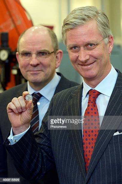 King Philippe of Belgium presents a one Euro coin bearing his effigy on February 4 , 2014 in Brussels, Belgium.