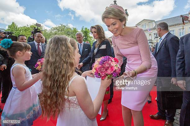King Philippe of Belgium Queen Rania of Jordan and Queen Mathilde of Belgium receive a bouquet of flowers as they arrive at the Town Hall during a...