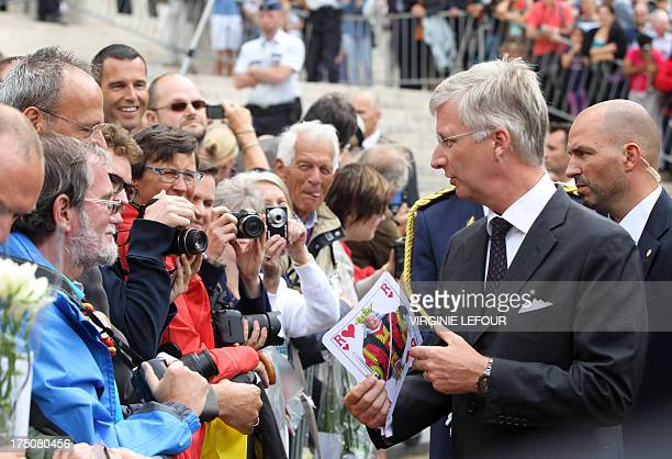 King Philippe of Belgium shakes hand with people and is offered gifts after as he leaves the Saint Michael and Saint Gudula Cathedral where he...