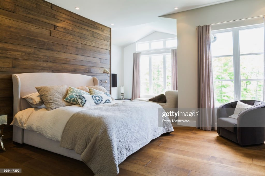 King size bed in bedroom with hickory wood floorboards : Stock Photo