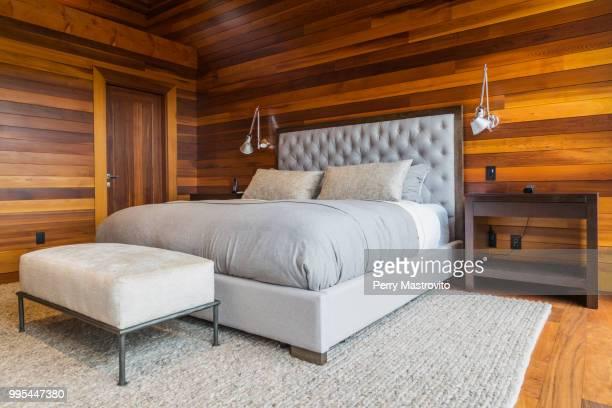 king size bed in master bedroom inside luxurious cedar wood home - ottomane stockfoto's en -beelden