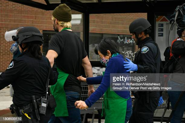 King Soopers' employees are escorted down the street by Boulder Police after being taken out of the supermarket after a shooting in the store at King...