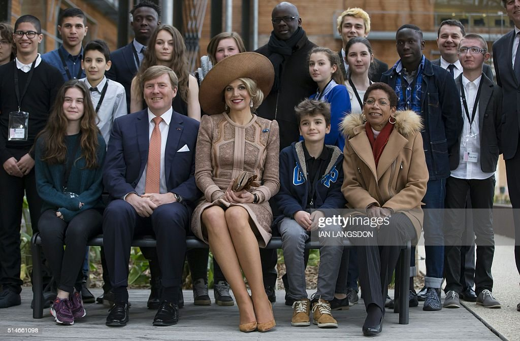 King Willem Alexander (2nd L) and Queen Maxima of the Netherlands (C), sitting on a bench which they gifted to a youth association, pose alongside French Minister for Overseas Territories George Pau-Langevin (front R), former French footballer Lilian Thuram (Rear C) and youths during their visit the Halle Pajol youth hostel in Paris on March 10, 2016 at the start of their two-day state visit to France. / AFP / POOL / IAN
