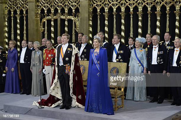 King Willem Alexander of the Netherlands and HM Queen Maxima of the Netherlands stand in front of their thrones near members of the royal household...