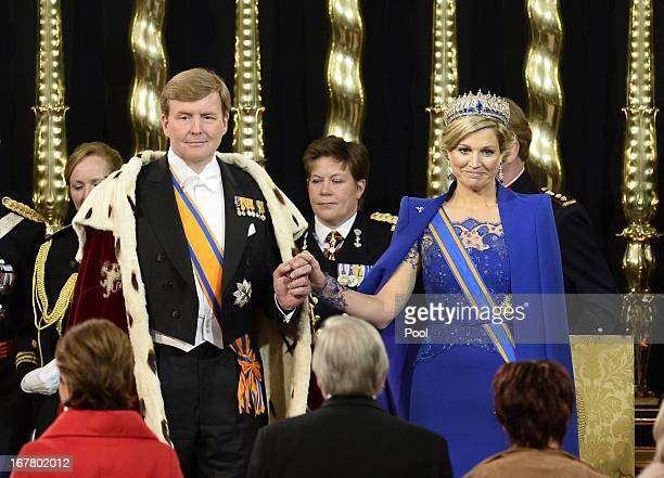 King Willem Alexander of the Netherlands and Queen Maxima of the Netherlands stand in front of members of the States General and the States of Aruba...