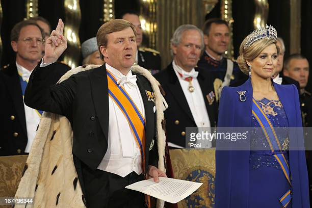 King Willem Alexander of the Netherlands takes the oath as his wife HRH Queen Maxima of the Netherlands looks on during their inauguration ceremony...