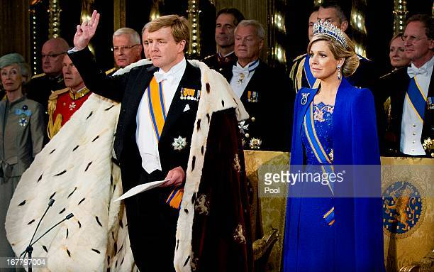 King Willem Alexander of the Netherlands takes the oath as HM Queen Maxima of the Netherlands looks on near members of the royal household during...