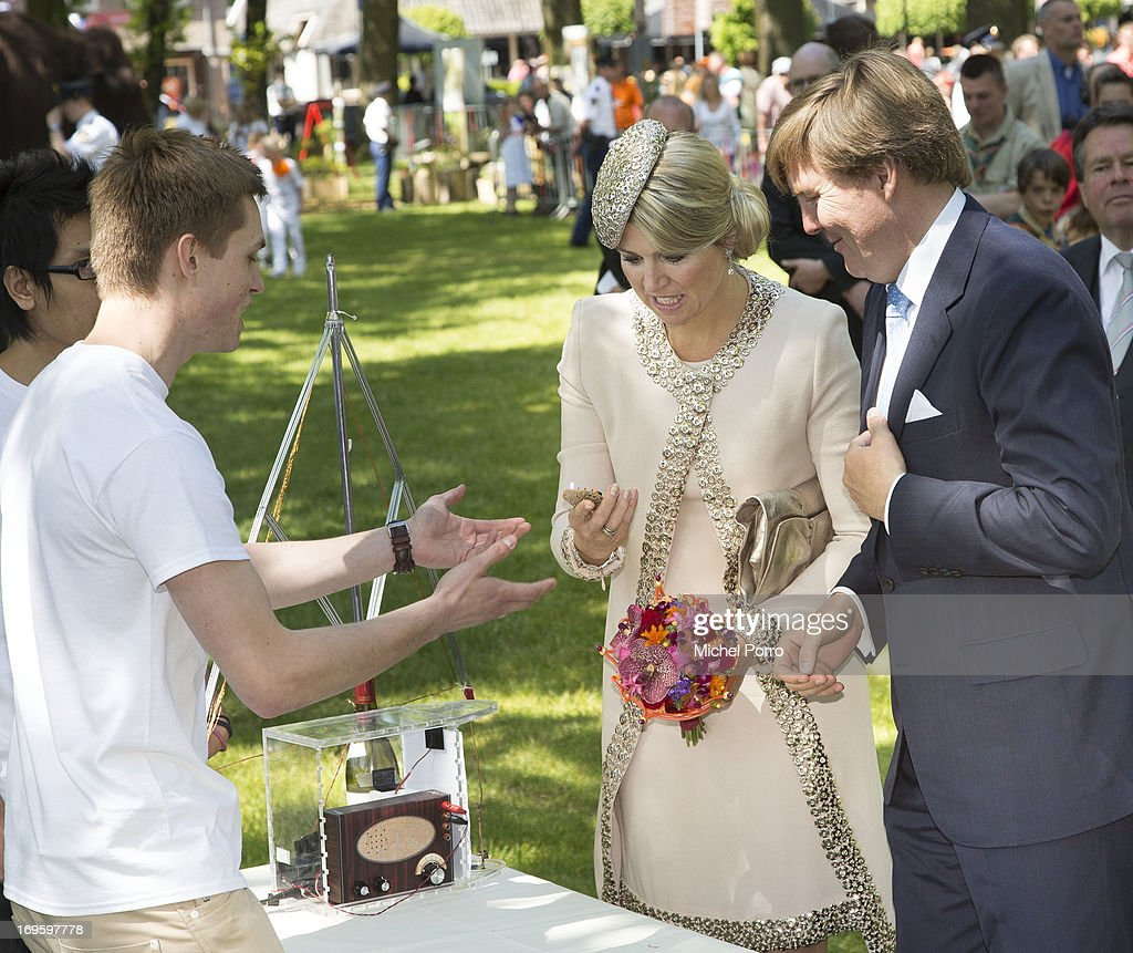 King Willem-Alexander and Queen Maxima of The Netherlands talk with a radio amateur during a one day visit to Groningen and Drenthe provinces at downtown Dwingelo on May 28, 2013 in Dwingelo, Netherlands.