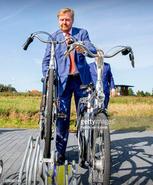 King Willem-Alexander of The Netherlands and Queen Maxima of The Netherlands park their bicycles as they visit ECOstyle, Biosintrum and EcoMinutypark...