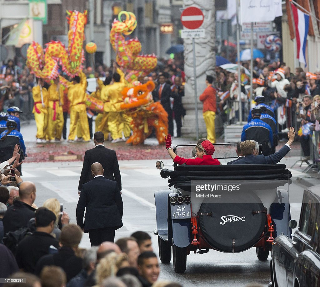 King Willem-Alexander of The Netherlands and Queen Maxima of The Netherlands take a ride in a classic car into the Chinese Quarter of The Hague where lion dancers perform on June 21, 2013 in The Hague, Netherlands.