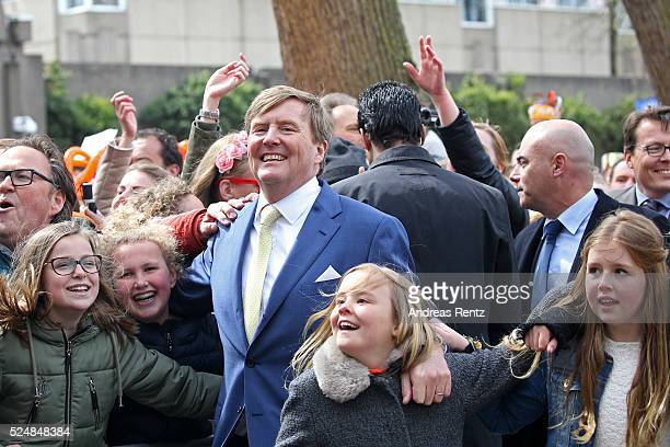 King Willem-Alexander of The Netherlands, Princess Ariane of The Netherlands and Princess Alexia of The Netherlands dance with spectators during...