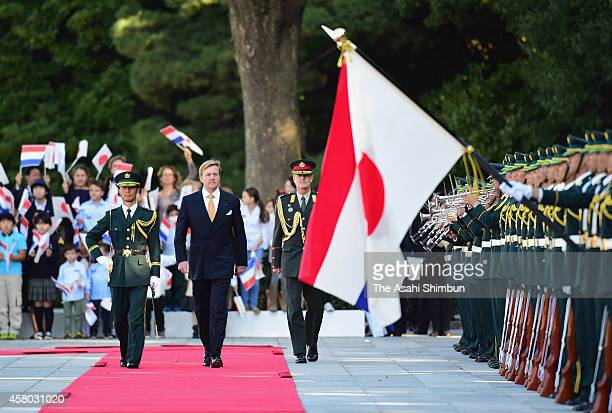 King WillemAlexander of the Netherlands reviews the honour guard during the welcome ceremony at the Imperial Palace on October 29 2014 in Tokyo Japan...