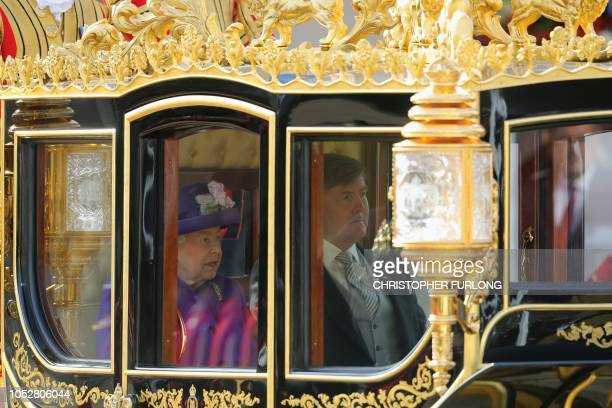 King WillemAlexander of the Netherlands sit beside Britain's Queen Elizabeth II as they travel by horsedrawn carriage to Buckingham Palace after a...
