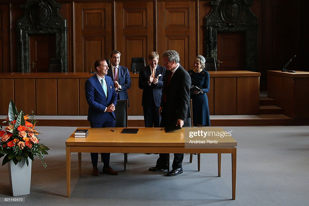 King Willem-Alexander, Queen Maxima of the Netherlands and Bavarian Minister of Ecnomic Affairs Markus Soeder (L) applaud Director of Grotius Centre Carsten Stahl and Director of INPA Bernd Borchardt after signing a letter of intent to start their co-operation in the famous courtoom 600 of Nuremberg trials on April 14, 2016 in Nuremberg, Germany. King Willem-Alexander and Queen Maxima are on a two-day visit in Bavaria to strengthen the relationship between Bavaria and the Netherlands.