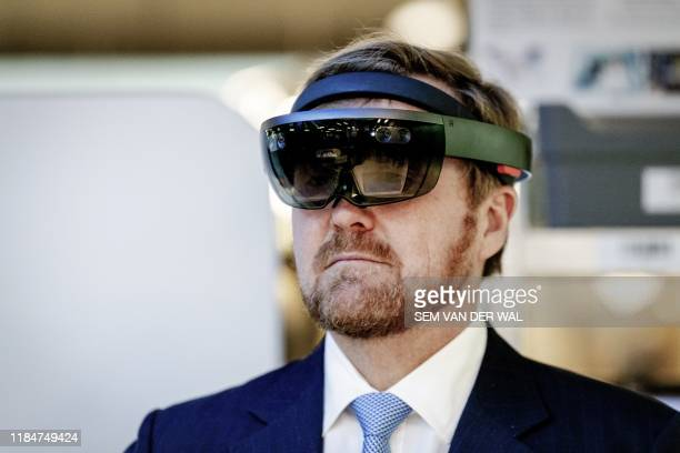 King WillemAlexander tries a virtual reality helmet as he visits the educational institution Fontys Venlo in Venlo the Netherlands on November 26...