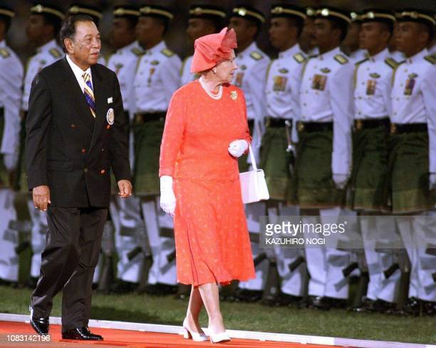 King Yang Dipertuan Agong of Malaysia and Queen Elizabeth of England inspect an Honor Guard during the closing ceremonies 21 September at the XVI...