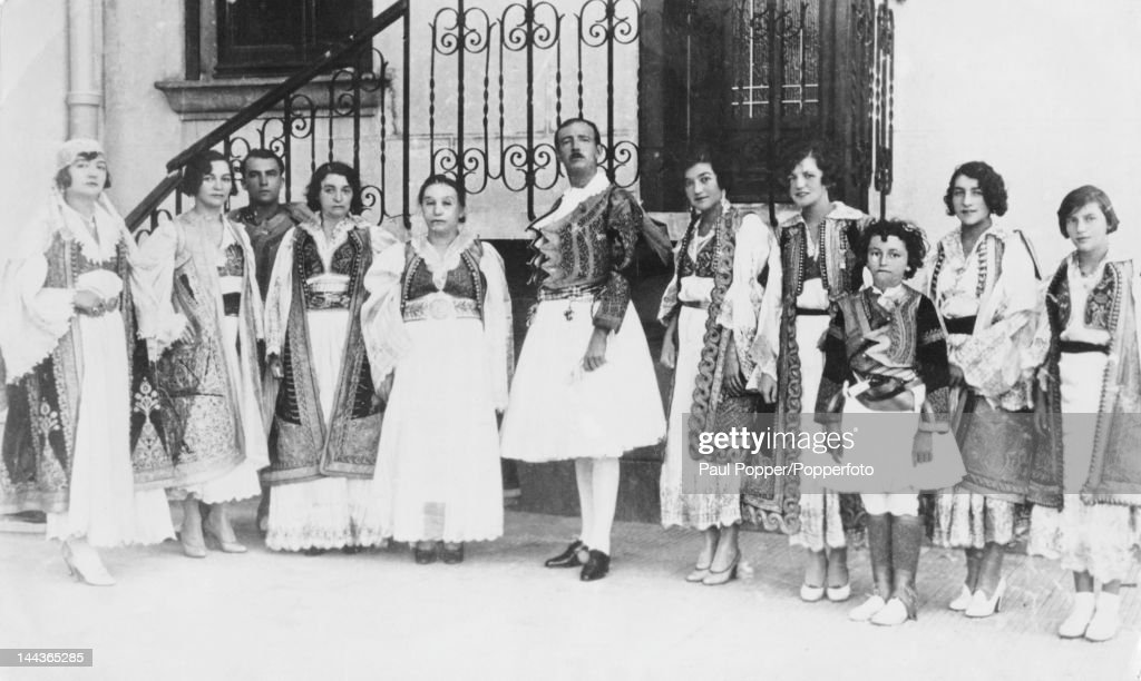 King Zog I of Albania (1895 - 1961, centre) and members of the Albanian Royal Family outside the Royal Palace in Tirana, circa 1930. Next to Zog (centre, left) is the Queen Mother, Sadije Toptani (1876 - 1934). Zog's elder half brother Xhelal Bey Zogu (1881 - 1944) is third from left. Among the family group are Zog's six sisters, the princesses Adila, Nafisa, Xenia, Muza Jan, Ruqiya and Majida as well as Princess Nafisa's son Tati Esad Murad Kryziu (1923 – 1993, third from right).