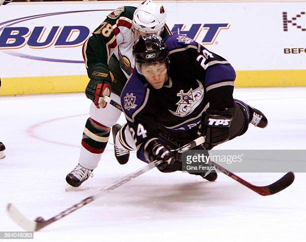 Kings Alexander Frolov dives for a puck near the goal with Minnesota Wild Todd White on his back during the first period at Staples Center in Los...