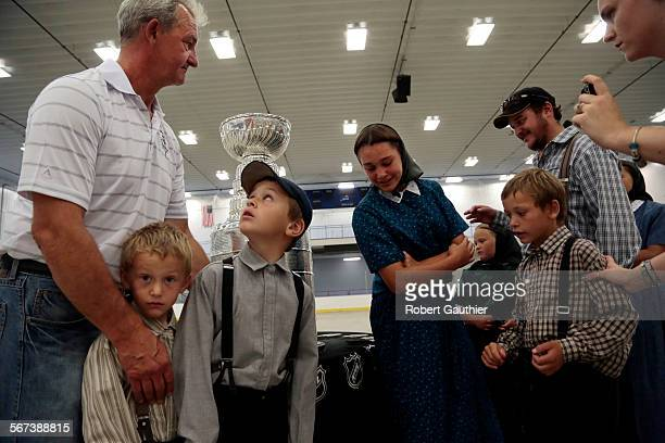 Kings coach Darryl Sutter greets members of the Edward Walter family as they gather for a photo near the Stanley Cup at the Viking Carena Complex...