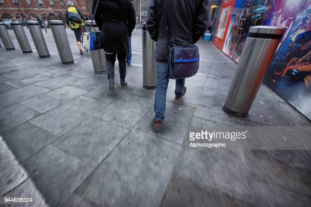 kings cross commuters walking past new developments - bollard stock photos and pictures