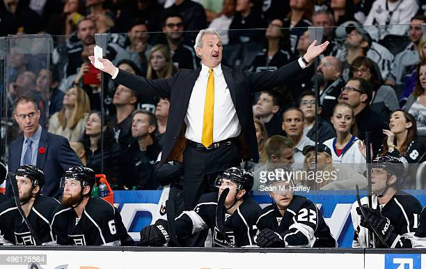 Kings Head Coach Darryl Sutter coaches from the bench while Jake Muzzin of the Los Angeles Kings Trevor Lewis of the Los Angeles Kings look on during...