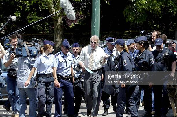 King's Prosecutor Michel Bourlet arrives surrounded by policemen the Arlon assize court 17 June 2004 Belgian childrapist Marc Dutroux was convicted...