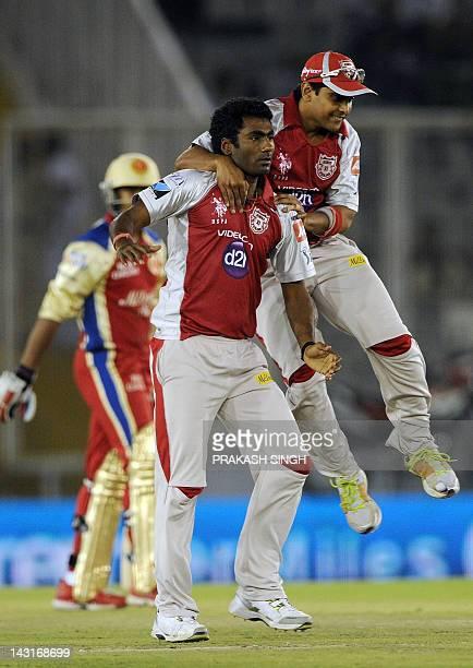 Kings XI Punjab bowler Parvinder Awana celebrates taking the wicket of Royal Challengers Bangalore batsman Mayank Agarwal with teammates during the...