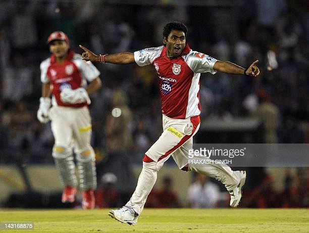 Kings XI Punjab bowler Parvinder Awana celebrates taking the wicket of Royal Challengers Bangalore batsman Virat Kohli during the IPL Twenty20...