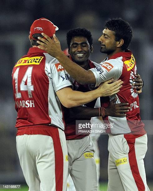 Kings XI Punjab bowler Parvinder Awana celebrates taking the wicket of Royal Challengers Bangalore batsman Virat Kohli with teammates during the IPL...