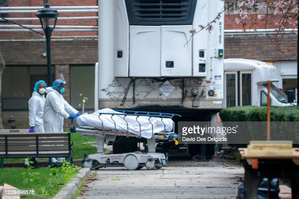 Kingsbrook Jewish Medical Center employees transport a deceased patient to a refrigerated truck on April 8, 2020 in the Brooklyn borough of New York...