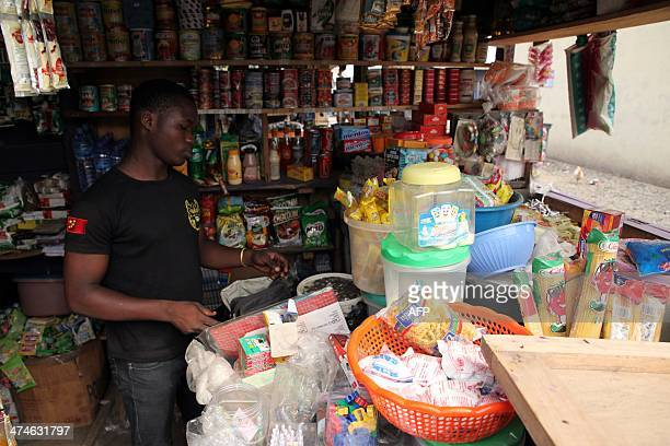 Kingsley Adukpo stands in his shop in Accra on February 11 2014 Adukpo had to repeatedly raise his prices due to the weakening Cedi Ghana's president...