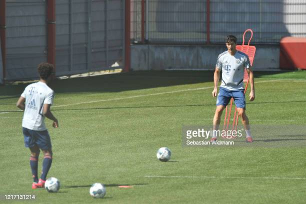 Kingsley Coman of Bayern Muenchen passes the ball to Robert Lewandowski during a training session at Saebener Strasse training ground on April 06...