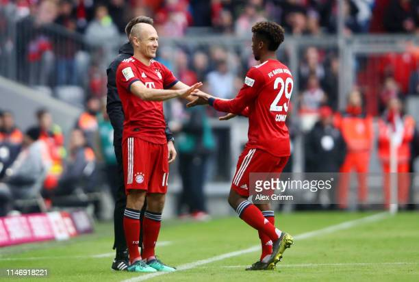 Kingsley Coman of Bayern Munich greets Arjen Robben of Bayern Munich as Arjen Robben is substituted on and Kingsley Coman is substituted off during...