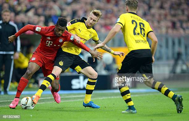 Kingsley Coman of Muenchen and Marco Reus of Dortmund compete for the ball during the Bundesliga match between FC Bayern Muenchen and Borussia...