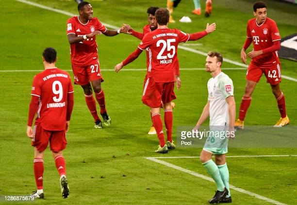 Kingsley Coman of Muenchen celebrates his team's first goal with teammates David Alaba and Thomas Mueller during the Bundesliga match between FC...