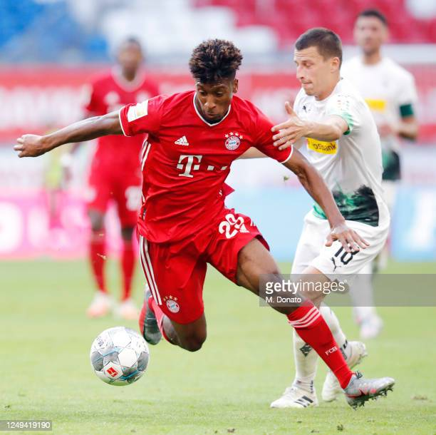 Kingsley Coman of Muenchen is challenged by Stefan Lainer of Moenchengladbach during the Bundesliga match between FC Bayern Muenchen and Borussia...