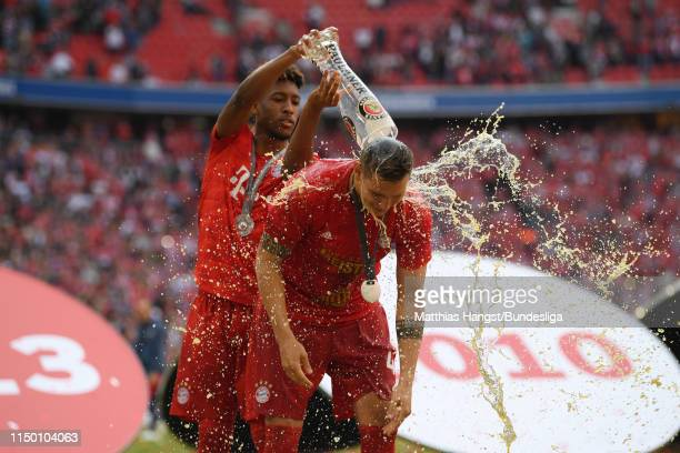 Kingsley Coman pours beer over Niklas Süle of FC Bayern München as they celebrate winning the title following the Bundesliga match between FC Bayern...