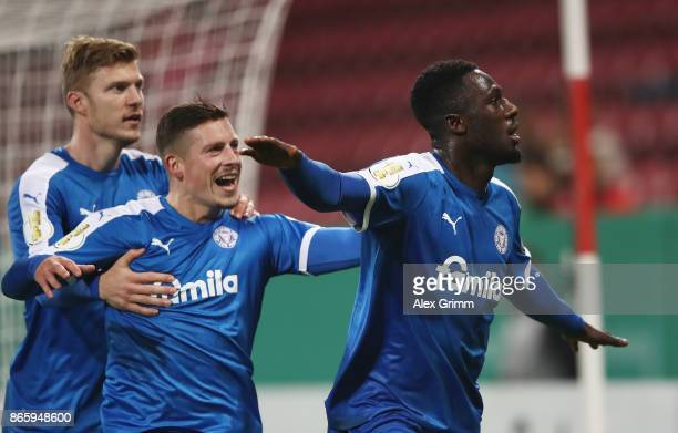 Kingsley Schindler of Kiel celebrates his team's first goal with team mates Steven Lewerenz and Alexander Muehling during the DFB Cup match between 1...