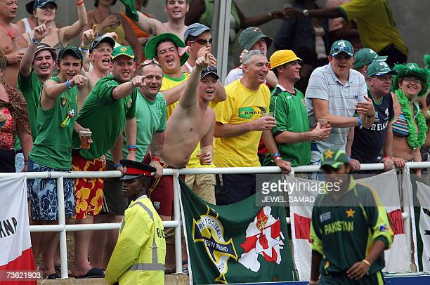 Irish cricket fans celebrate as Pakistani cricketer Danish Kaneria walks past during the Group D match of the ICC World Cup 2007 between Ireland and...