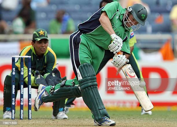 Irish cricketer Niall O'Brien hits a boundary off Pakistani bowler Mohammad Hafeez as wicketkeeper Kamran Akmal looks on during the Group D match of...