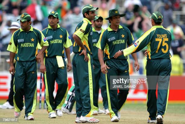 Pakistani crickters dejectedly look at Irish cricketers who are celebrating after defeating them at the end of the Group D match of the ICC World Cup...