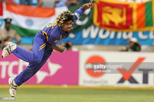 Sri Lankan cricketer Lasith Malinga bowls to New Zealand against a backdrop of the Indian, Pakistan and Sri Lankan flags during the ICC Cricket World...
