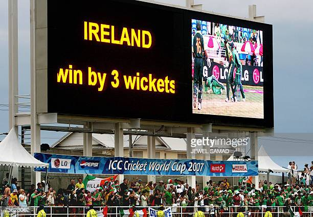 The electronic scoreboard shows the result as Irish cricket fans celebrate their team's victory over Pakistan at the end of the Group D match of the...