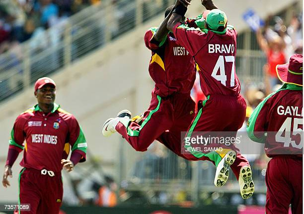 West Indies cricket captain Brian Lara smiles as bowler Jerome Taylor gets airborne with teammate Dwayne Bravo to celebrate taking the wicket of...