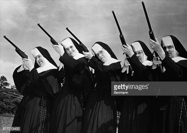 Sisters of Divine Providence set their sights as they try out new 22 caliber guns presented to them at camp Mishannock by Harrington and Richardson...