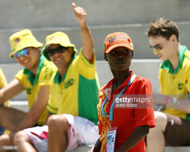 Kingstown, SAINT VINCENT AND THE GRENADINES: A spectator usher stands near Australian fans as they watch the action during the Cricket World Cup...